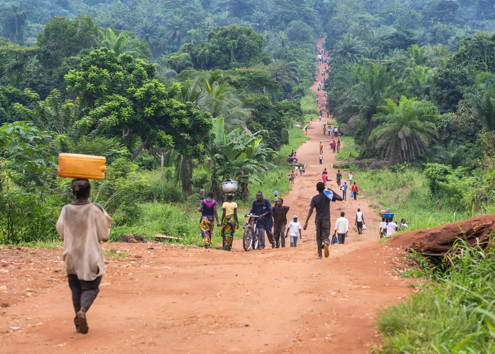 People walk on an unpaved road in DR Congo